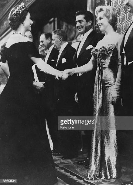 Queen Elizabeth II shaking hands with Marilyn Monroe who stands next to Victor Mature at a Royal Film Performance of 'The Battle of the River Plate'...