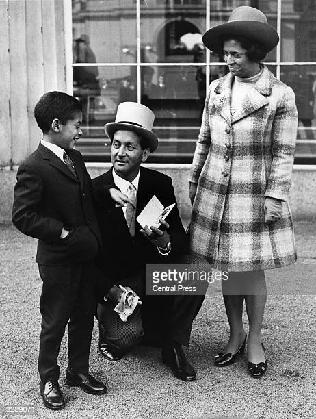 Basil D'Oliveira the England Test cricketer shows his son Damien his OBE at Buckingham Palace London His wife is on the right