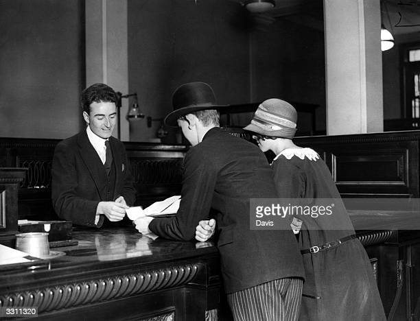 A bank clerk paying out to two customers