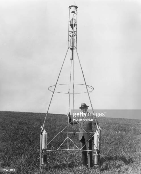 American physicist Dr Robert Goddard poses in a field behind a rocket set in a frame with the combustion chamber and nozzle at the top