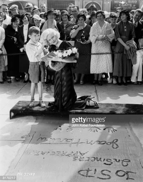 Young fan and MGM star Jean Harlow who has been leaving an impression of her handprints and a message in the wet cement on the pavement outside...