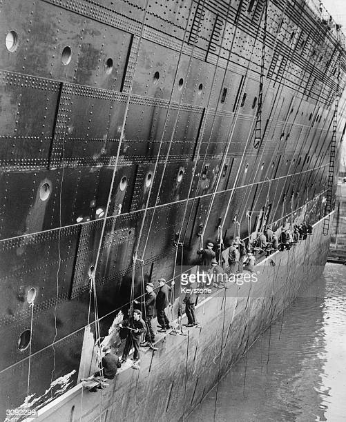 A row of workmen balancing on suspended planks scrape old paint off the starboard bow of the Cunard White Star liner Queen Mary in preparation for a...