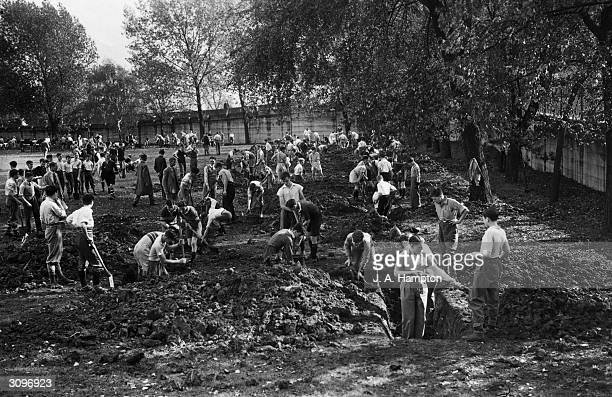 Pupils from the Harrow County School in Harrow Middlesex dig trenches around the school playing field as part of their World War II air raid...