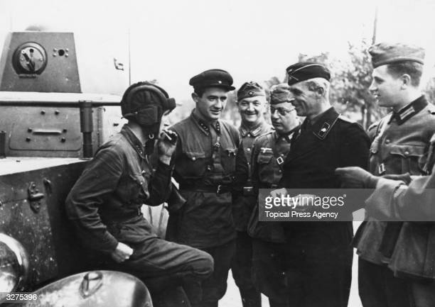 German officers and soldiers in Poland chatting with the crew of a Russian tank