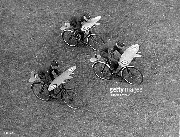 Three boys from the RAF's Coulsdon and Purley Squadron practice 'formation flying' using bicycles with little wings over the handlebars
