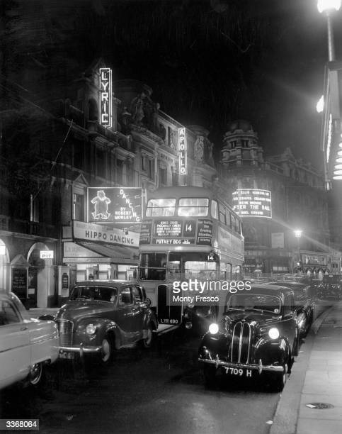 A bus and cars travelling down Shaftesbury Avenue London in front of an illuminated Lyric Theatre at night
