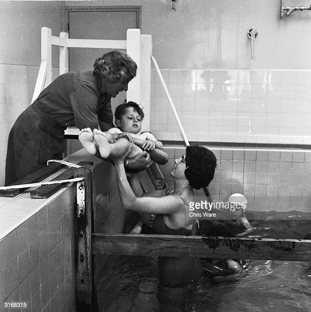 John is handed by a WVS helper to a physiotherapist in the warm water pool for hydrotherapy treatment for juvenile rheumatism at the Canadian Red...