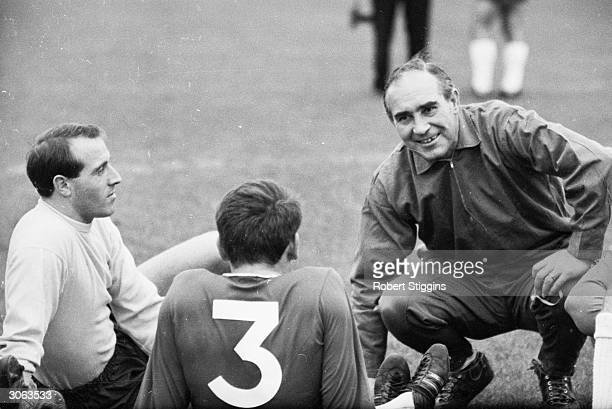 England manager Alf Ramsey talks to two players during a trial match against Chelsea FC