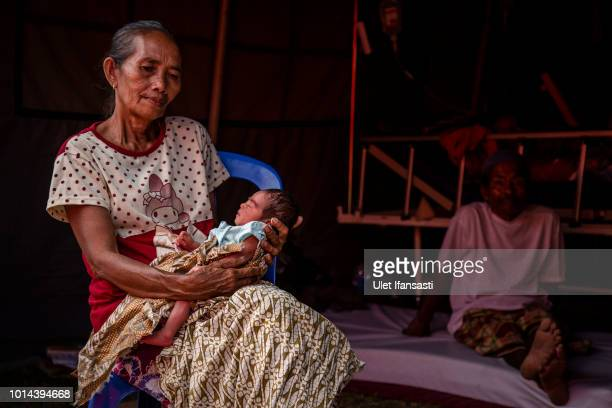 A 2dayold baby Gempa Maulana carried by his grandmother at an emergency hospital following Sunday's earthquake and a series of aftershocks in Tanjung...