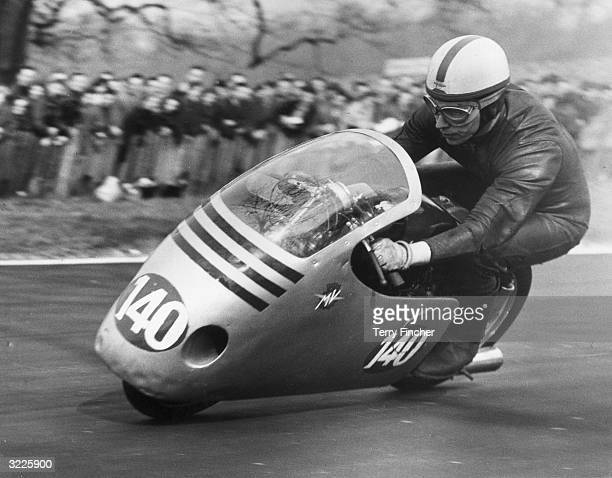British motorcyclist and racing driver John Surtees riding an MV Agusta during the final lap of the 250 cc event at Crystal Palace Surtees won with a...
