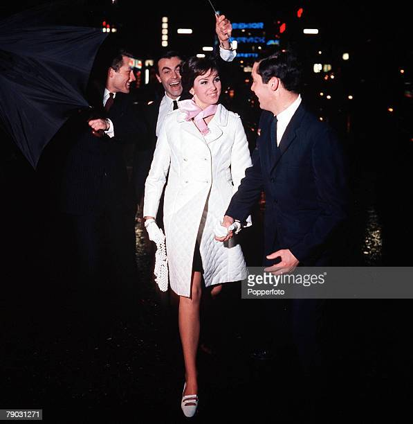 2nd April 1966 A picture of an elegant fashionable young woman wearing white coat whilst accompanied by three smartly dressed happy young men with...