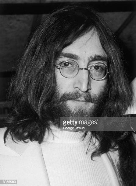 Singer songwriter and guitarist John Lennon of The Beatles at a press conference at Heathrow airport
