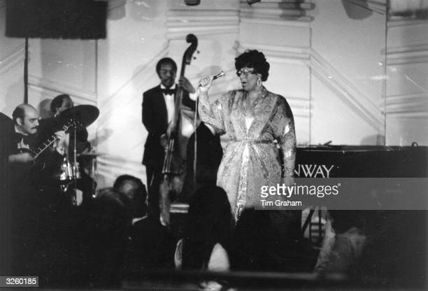 American jazz scat singer Ella Fitzgerald performing at Ronnie Scott's jazz club in London, with Joe Pass on guitar, left.