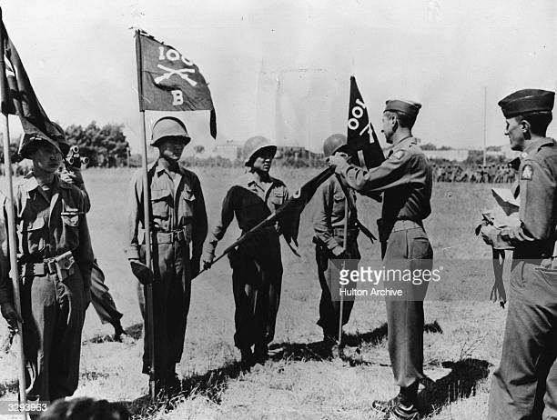 American General Mark Clark commander of the Allied Fifth Army in Italy fastens the citation streamers on the quidons of the 100th battalion flag as...