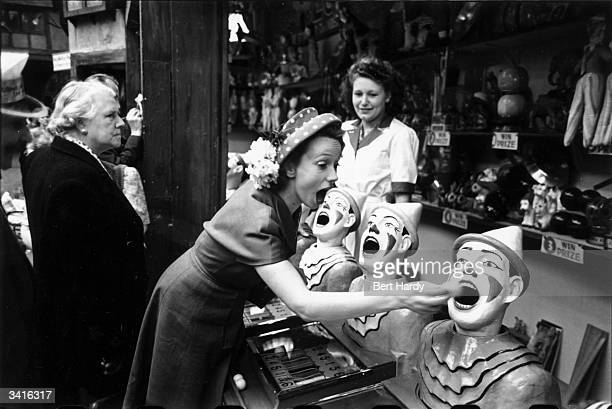 French film actress Mila Parely at a funfair stall on the Southend Kursaal SouthendonSea Essex Original Publication Picture Post 4412 Mila Goes To...
