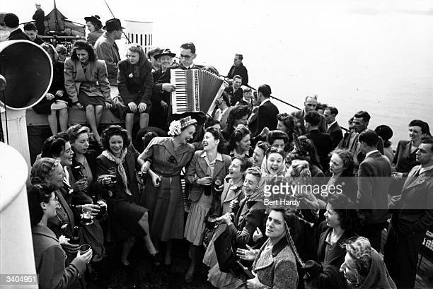 French film actress Mila Parely enjoys a song with passengers crowded onto the deck of a ferry from Tower Bridge London to Southend Essex Original...