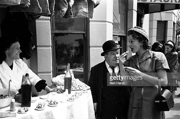 French film star Mila Parely eating a cockle in Southend Original Publication Picture Post 4412 Mila Goes To Southend pub 1947