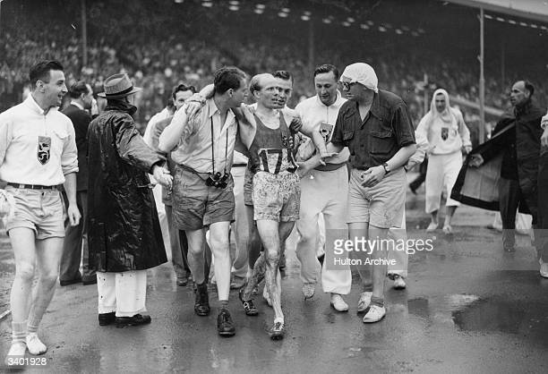 Gaston Reiff of Belgium is led from the track after winning the 5000 metres final in the rain at the 1948 Olympics at Wembley London