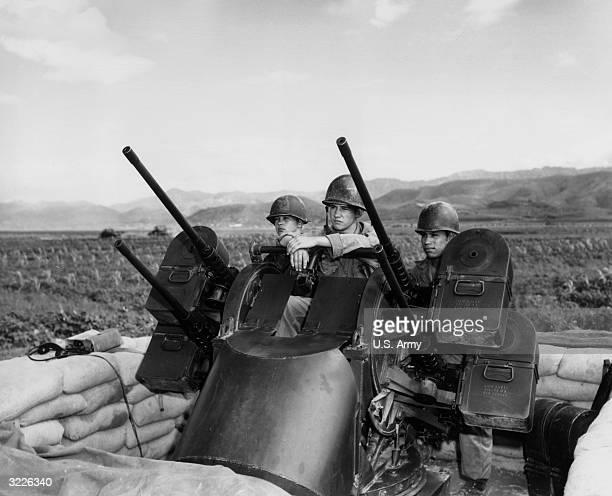Three US soldiers man an M55 multiple antiaircraft machine gun turret behind sandbags during the Korean War Korea LR Private Charles S Vaughn...