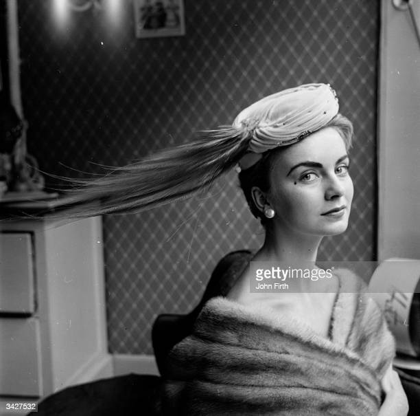 A model wearing a Madge Chard millinery creation with a sweeping bunch of feathers