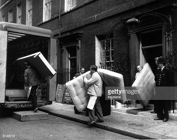 Workmen carrying out mattresses from Number 10 Downing Street, London, in preparation for the two-year rebuilding scheme of the premises.