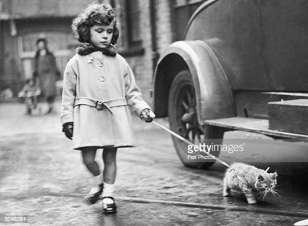 Young exhibitor arrives with her kitten on a lead at the National Cat Club show at Crystal Palace, London.