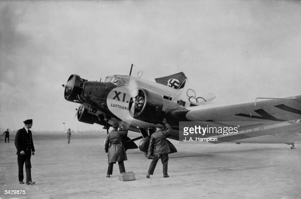 Employees of Deutsche Lufthansa air line giving a Nazi salute as a plane flying a Nazi flag and carrying the German Olympic Games Committee lands at...