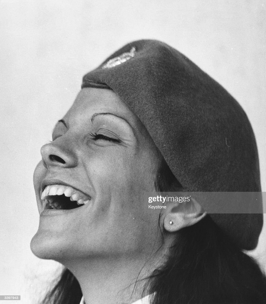A woman soldier laughing. She is taking part in a Military Parade in Cuba to mark the anniversary of the Cuban Revolution in 1956.