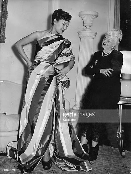 Dress designer Madame Nina Ricci on the right casting a critical eye at a mannequin whom she has draped with material to make an instant dress Madame...