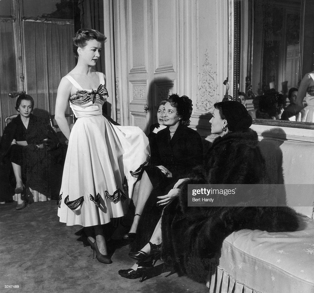 Model Ghislaine de Boysson modelling a white dress with tartan trim for clients at Mme Schiaparelli's Fashion House. Original Publication: Picture Post - 5664 - Princess Margaret's Stand In - pub.1952