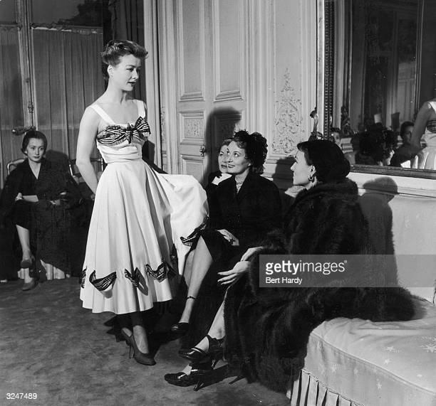 Model Ghislaine de Boysson modelling a white dress with tartan trim for clients at Mme Schiaparelli's Fashion House. Original Publication: Picture...