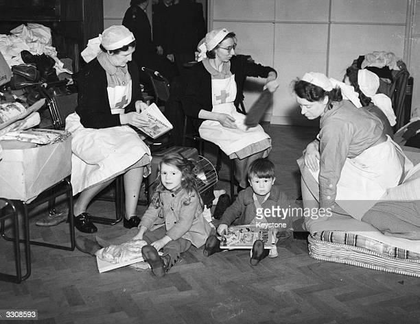 Children playing on the floor of the Red Cross headquarters after the great floods which swept the Essex and Kent countryside