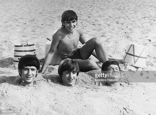 Three members of American pop group The Monkees have been buried up to their necks in sand by fellow group member Davy Jones Buried members are left...