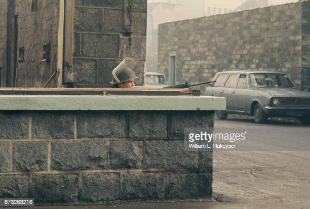 2nd February 1972 A soldier takes cover behind a wall in Newry prior to a civilian protest organised in response to the shooting of 14 civilians by...