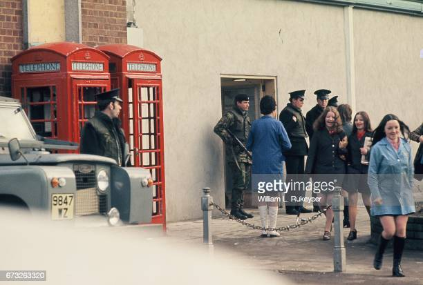 2nd February 1972 Young women laugh as they walk past police and soldiers prior to joining the Northern Irish Civil Rights Assn march in Newry a...
