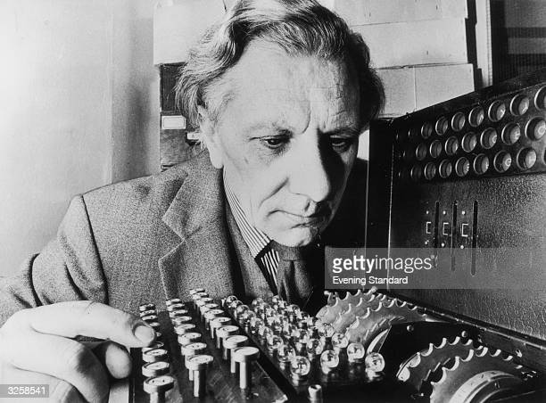 The Enigma decoding machine used during World War II being inspected by Ryszard Dembinski, museum director.