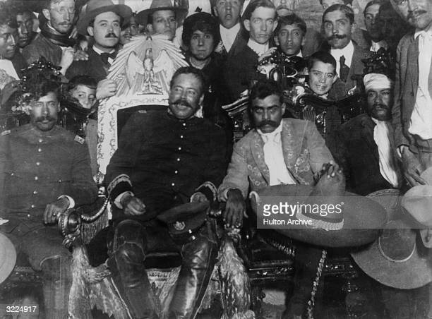 Mexican revolutionaries Pancho Villa and Emiliano Zapata sit with Tomas Urbina and Otilio Montano