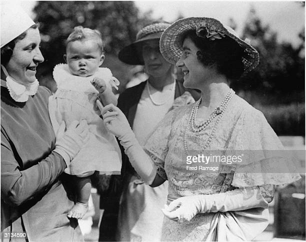 Elizabeth, Duchess of York, later the Queen Mother meets little Ann Smith at St James' Palace, London, during a garden party in aid of the National...