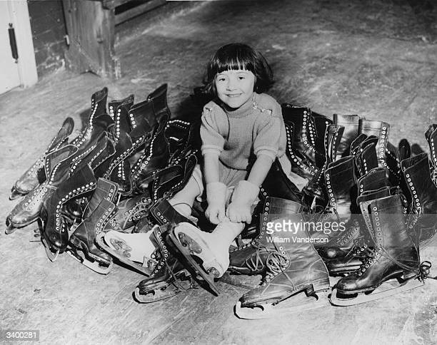 One of the country's youngest skaters four year old Beryl Bailey surrounded by ice-skating boots at Haringey Arena, London.