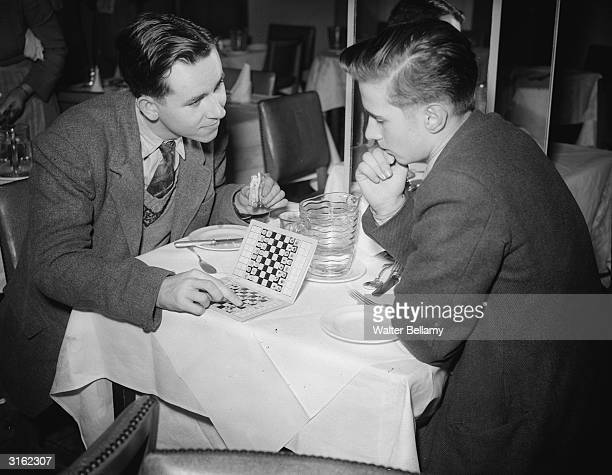 British chess champions Jonathan Penrose and Leonard Barden ponder over a portable travel game in a restaurant