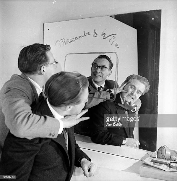 British comedians of stage and screen Eric Morecambe and Ernie Wise messing around in front of a mirror Original Publication Picture Post 6849 The...