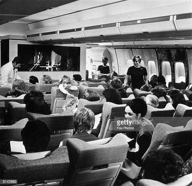 BOAC air stewards tend to rows of passengers seated in the new Boeing 747 widecabined jumbo jet