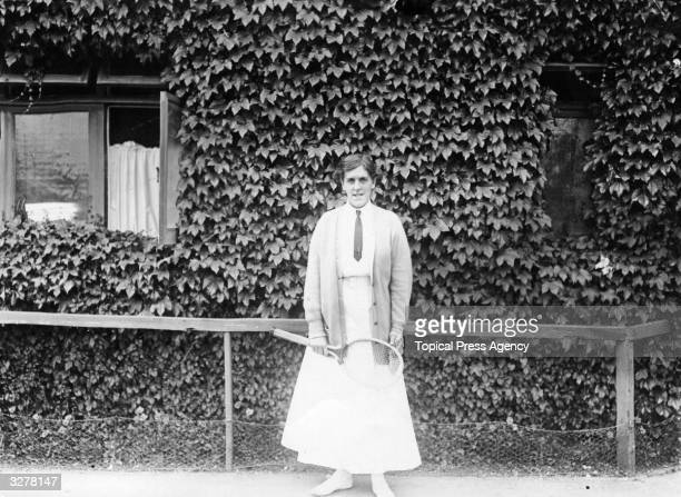 British tennis player Dorothea Lambert Chambers standing beside an ivyclad wall at the All England Tennis Club during the Wimbledon Championships