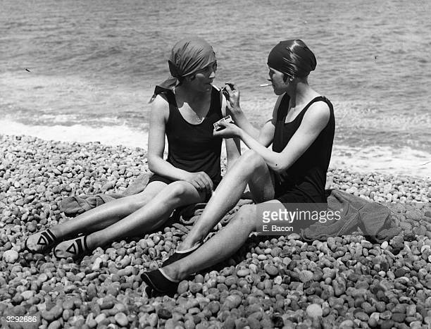 Two bathers enjoy a cigarette on the beach at Lowestoft