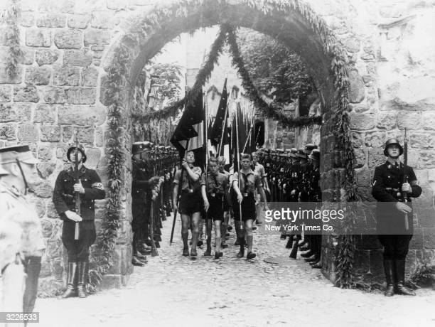 Fulllength image of members of the Hitler Youth carrying flags while marching past Nazi troops through the gates of the Quedlinburg castle...
