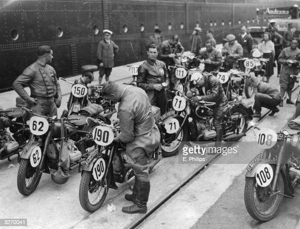 German motorcyclists including two army teams of Storm Troopers attending to their machines on arrival in Southampton for the International Six Days...