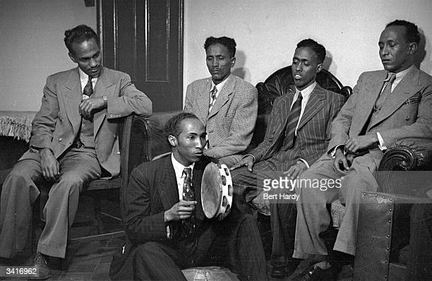Four men listening to another playing a tambourine Original Publication Picture Post 4825 Is There A British Colour Bar pub 1949