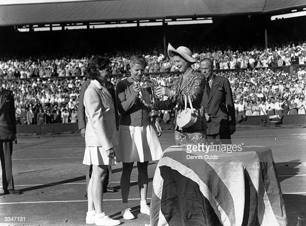 Margaret du Pont of the USA and Louise Brough of the USA collecting the Women's Doubles Trophy from the Duchess of Kent after beating Gussie Moran...
