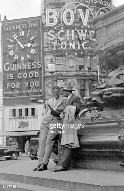 Two men leaning on the base of the Eros statue in Piccadilly Circus London Original Publication Picture Post 4825 Is There A British Colour Bar pub...
