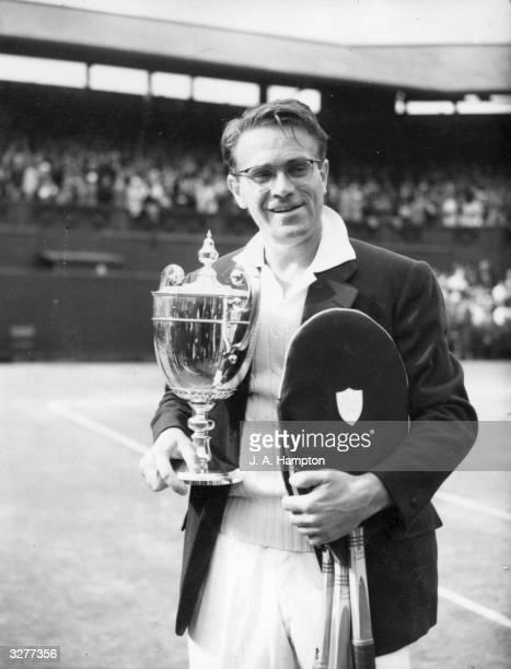 Czechborn Egyptian tennis player Jaroslav Drobny holding the men's singles trophy after beating Ken Rosewall of Australia at the Wimbledon Lawn...